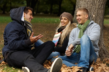 Young friends sitting on ground among leaves in autumn park, talking, smiling. photo