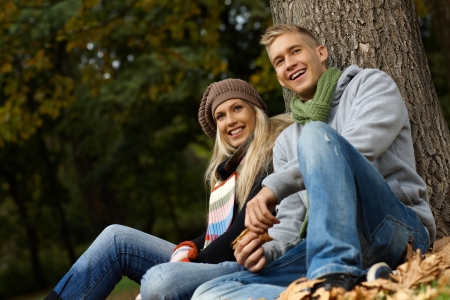 Attractive young couple sitting on ground in autumn park, smiling. photo