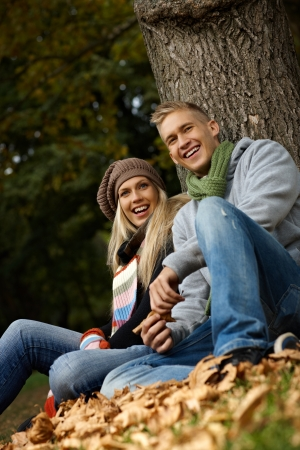 Smiling young couple sitting on ground among fallen leaves, having fun in autumn park. photo