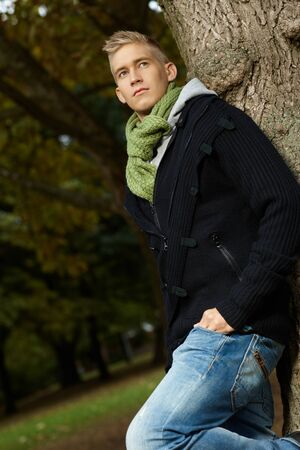 Young man leaning against tree in park, thinking, looking away. photo
