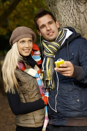 Attractive young couple listening to music, using mp3 player in park at autumn, smiling. photo
