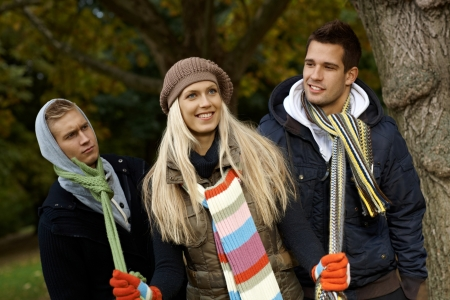 2 3 years: Beautiful girl in park pulling two boys by scarf, smiling.