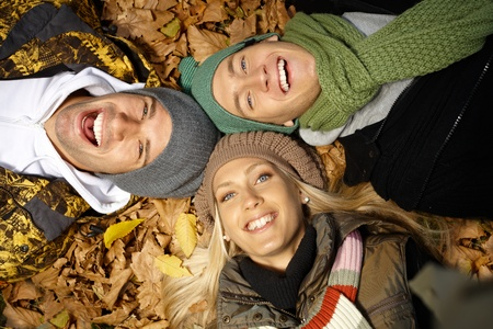 fellowship: Attractive young people laying on ground among autumn leaves, smiling, having fun. Stock Photo
