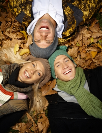 fall fun: Happy young people laying among leaves in autumn park, laughing, enjoying themselves.