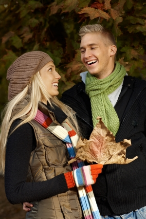 Happy young couple laughing in autumn park. photo