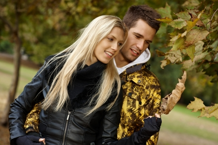 Young loving couple walking in autumn park, smiling. photo