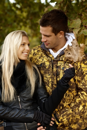 Attractive young couple in autumn park, hugging, smiling. photo