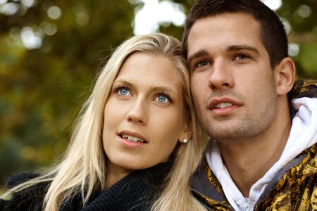 Portrait of attractive young loving couple, looking away. photo