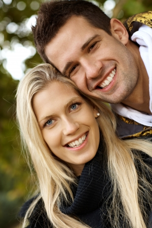 Portrait of happy loving couple in park, smiling, looking at camera. photo