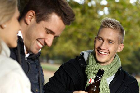 compa�erismo: Compa��a joven que sonr�e al aire libre, hablando, bebiendo en oto�o.
