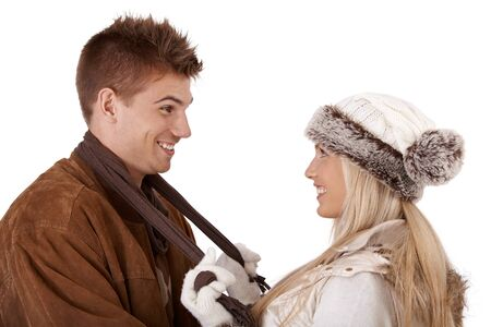 Happy couple in winter clothes, laughing at each other, wearing hat, scarf, coat and gloves, cutout on white. photo