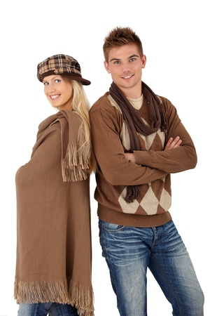 Trendy young couple posing in winter clothes, wearing scarf, hat, smiling at camera. photo