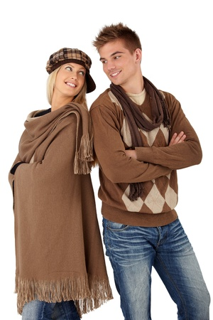 seasonal clothes: Portrait of happy couple posing in warm clothes, scarf and hat, standing together with arms crossed, smiling.