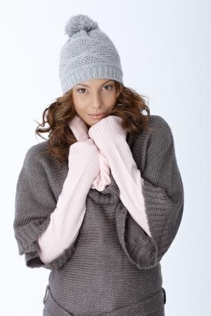warm clothes: Inverno ritratto di ragazza attraente in abiti cappello e caldo, su sfondo bianco.