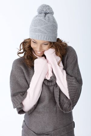 Happy woman in winter outfit smiling over white background, wearing hat and warm sweater. photo