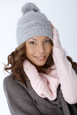 Beautiful ethnic woman dressed for winter, smiling, looking at camera. photo
