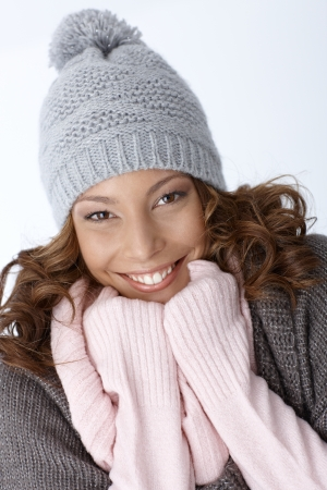 Beautiful ethnic girl smiling happily in winter outfit, wearing hat. photo