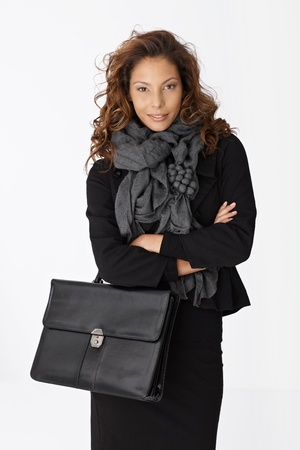 Portrait of attractive young businesswoman holding briefcase, smiling. photo