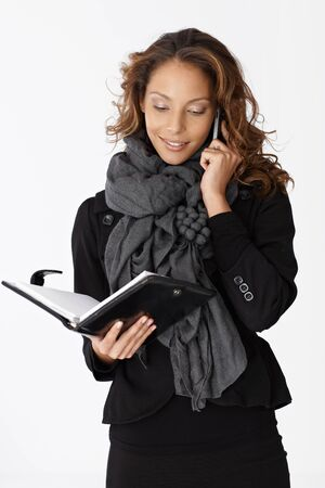 Young businesswoman on mobilephone, looking at personal organizer. photo