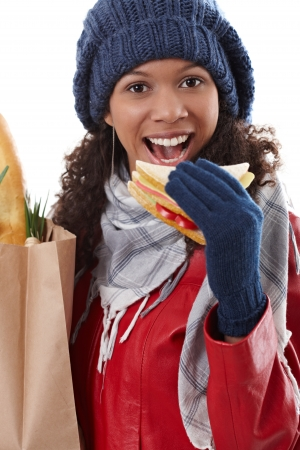 Winter portrait of attractive afro-american woman holding shopping bag, biting club sandwich, smiling. photo