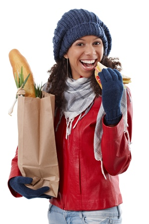 Happy ethnic girl holding shopping bag, eating sandwich at wintertime. photo