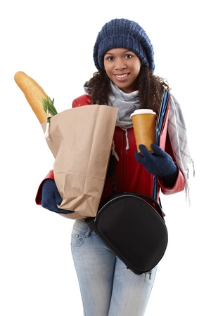 Ethnic woman loaded by shopping bag, shoulder bag, folder and coffee, smiling. photo