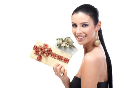 Attractive young woman holding fancy Christmas envelopes tied by ribbon, wearing Christmas ornament in ear, smiling. photo