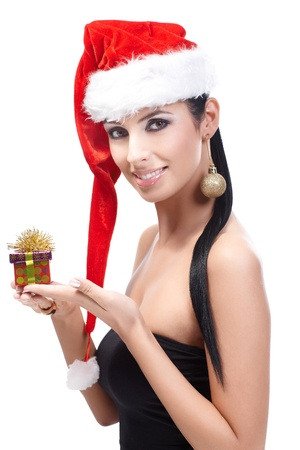 Attractive woman in santa hat holding small Christmas box, wearing Christmas ornament in ear, smiling, looking at camera. photo
