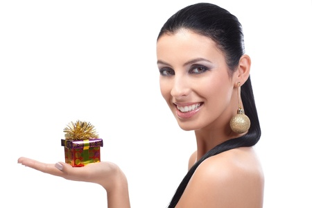 holding a christmas ornament: Attractive young woman holding a small Christmas box in hand, smiling, wearing Christmas ornament in ear.
