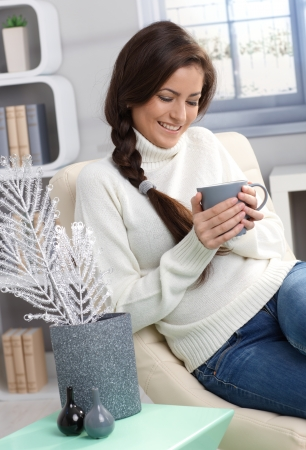Smiling woman enjoying hot tea at winter, sitting in cosy living room. photo