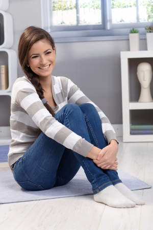 full size: Full size portrait of beautiful young woman sitting on floor at home, arms folded around knee, smiling happily.