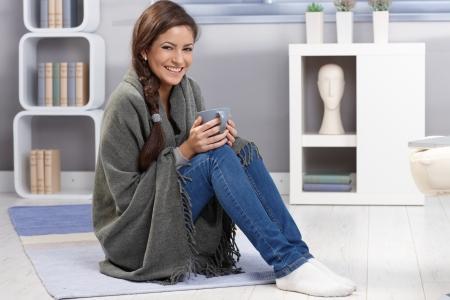 bebidas frias: Invierno retrato de ni�a feliz riendo, abrazando con una manta y una taza de t� en el piso de sala de estar.