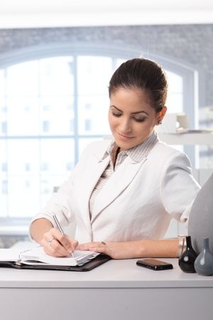 Smiling smart businesswoman taking notes into personal organizer in office. photo