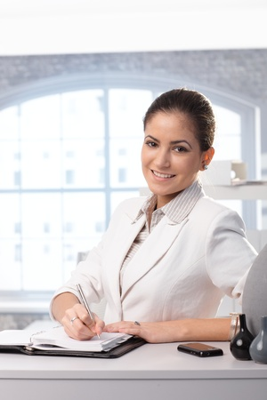 Portrait of young smiling businesswoman writing into personal organizer in office. photo