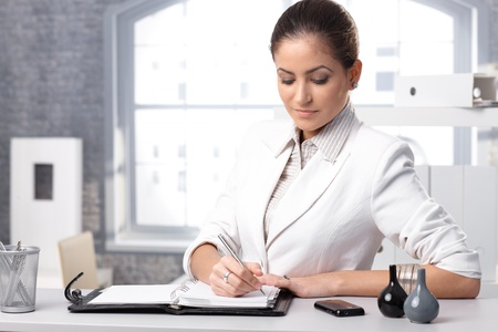 Businesswoman concentrating, taking notes at office desk. photo