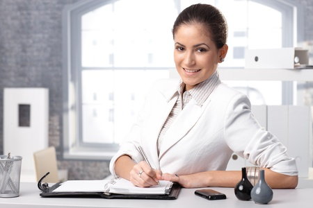 Portrait of young smart businesswoman writing notes, smiling at camera. photo