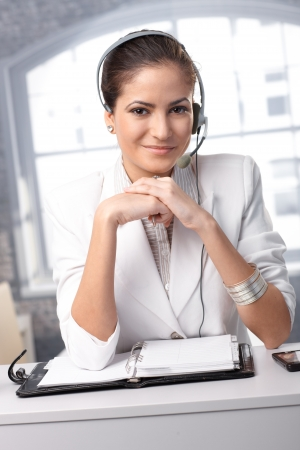 Confident customer service operator at office desk wearing headset, smiling at camera. photo