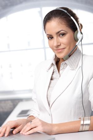 recepcionista: Retrato de representante de confianza del cliente inteligente y atractiva la atenci�n sonriendo a la c�mara.