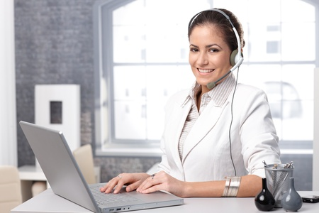 Portrait of happy call dispatcher working with laptop computer and headset in office.