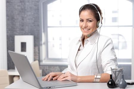 recepcionista: Retrato de distribuidor de llamadas feliz de trabajar con el ordenador port�til y un auricular en el cargo. Foto de archivo