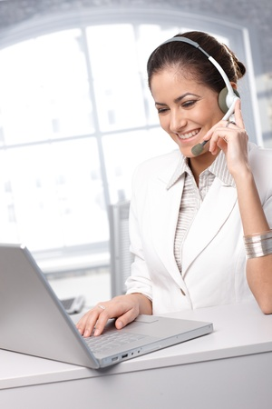 Dedicated customer service representative working on laptop computer, using headset, smiling. photo
