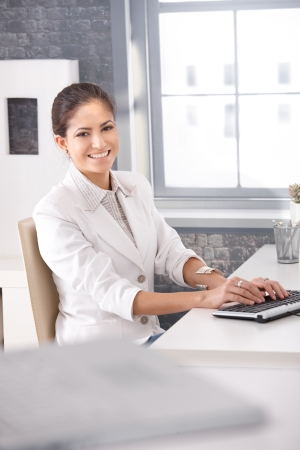 Portrait of happily smiling businesswoman sitting at office desk typing on keyboard. photo
