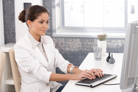 Young businesswoman working at office desk, typing on keyboard, smiling. Stock Photo - 14426309
