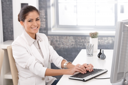 Happy office girl sitting at desk working on computer, typing on keyboard, smiling, Stock Photo - 14426397