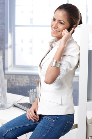 Pretty casual business woman sitting on office desk in jeans, talking on mobile phone, smiling. Stock Photo - 14426750