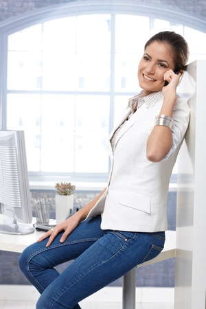 Casual portrait of happy businesswoman using mobile phone, sitting on office desk in jeans. Stock Photo - 14426775