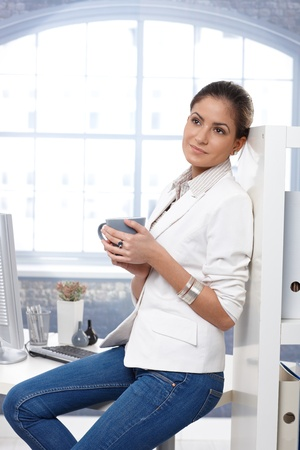 Portrait of casual attractive businesswoman thinking with tea mug handheld, sitting on office desk. Stock Photo - 14426582