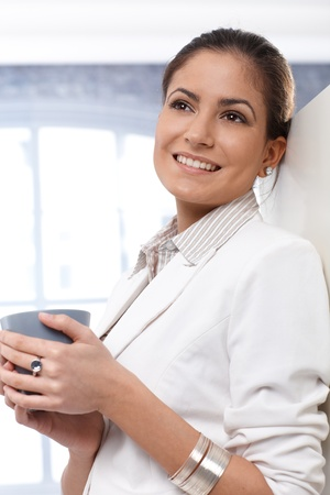 Portrait of happy businesswoman taking coffee break, thinking, daydreaming, smiling. Stock Photo - 14426464