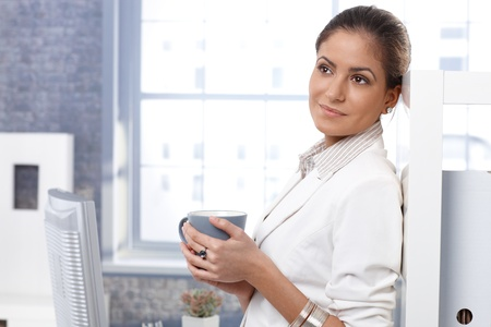 Portrait of attractive young businesswoman drinking tea in office, thinking, smiling, looking away. Stock Photo - 14426380