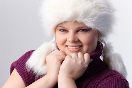 Portrait of overweight woman in white fur hat, smiling. photo